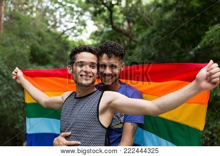 Gay Couple Embracing with Rainbow Flag in the Park