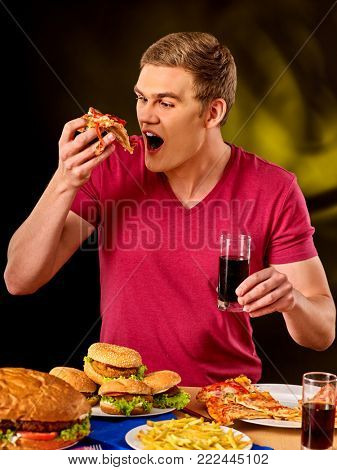 Young man eating slice of pizza . Fastfood concept. Dinner for the student.