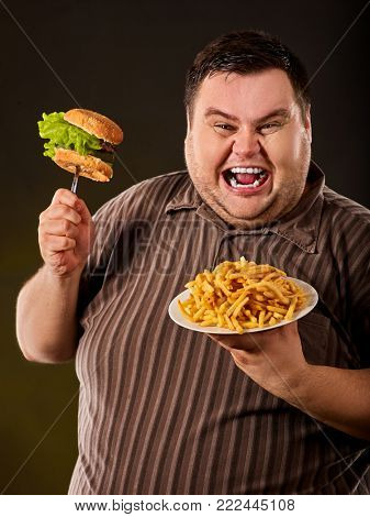Breakfast for overweight person.e of fat man eating fast food hamberger. Happy smile overweight person who spoiled healthy food by eating huge hamburger on fork. Food is main thing in life.