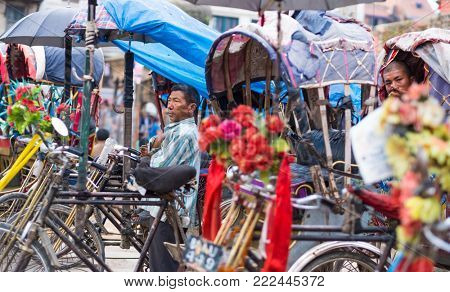 Kathmandu, Nepal - 06 October 2017: Rickshaw driver stand among other rickshaw and waits for clients