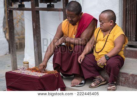 Kathmandu, Nepal - 06 October 2017: Two tibetian monks in traditional costumes sold some stuff at Boudhanath Stupa in Kathmandu, Nepal