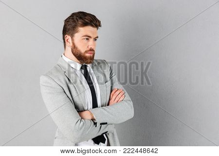 Portrait of a confident businessman dressed in suit standing with arms folded and looking away isolated over gray background
