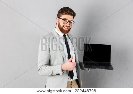 Portrait of a smiling businessman dressed in suit and eyeglasses showing thumbs up and holding blank screen laptop computer isolated over gray background