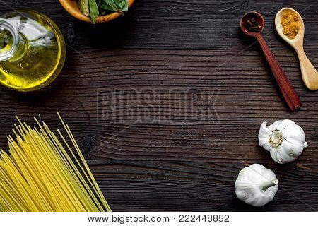 Cook a meal. Template for menu design. Mock up for menu or recipe. Empty space near ingredients. Raw pasta, oil, garlic, spices on dark wooden background top view.