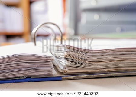 Open folder with documents on table in archive, closeup