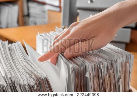 Woman searching for documents in archive, closeup