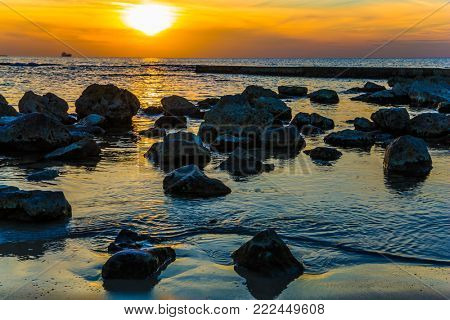 Large stones in tidal waves. Bright sunset on the coast of the Mediterranean Sea in Caesarea. Warm winter in Israel. Concept of ecological tourism