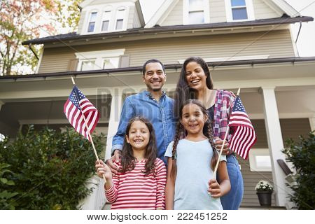 Portrait Of Family Outside House Holding American Flags