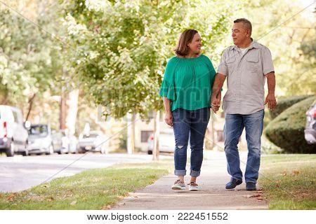Senior Couple Walking Along Suburban Street Holding Hands poster