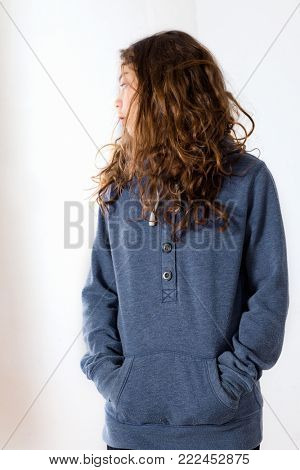 Teen with lazy face wearing a blue sweatshirt while posing