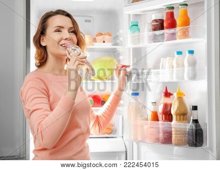 Beautiful woman drinking cold water from bottle near refrigerator