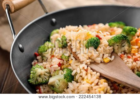 Delicious rice pilaf with broccoli in wok, closeup
