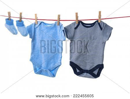 Children's clothes on laundry line against white background
