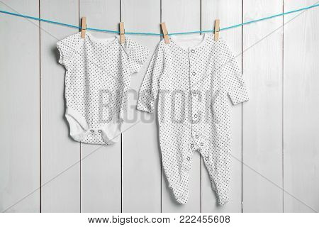 Children's clothes on laundry line against wooden background