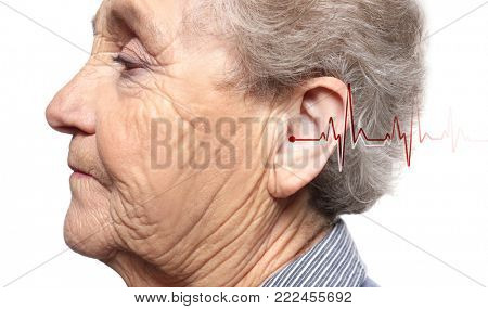 Senior woman with symptom of hearing loss on white background