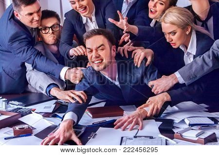 Business people office. Team people are unhappy with their leader. Intern man manager does not cope with his duties. Crowd in stress throw up their chief's papers. New director of firm.