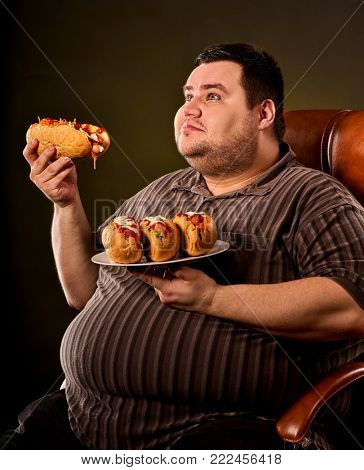 Fat man eating fast food hot dog on plate. Breakfast for overweight person. Junk meal leads to obesity. Person regularly overeats concept on black background. Food is main thing in life.