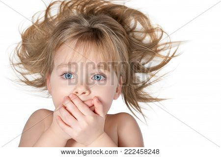 Little beautiful girl with blue eyes and tousled hair covered her mouth with her hands, isolated on white background