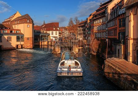 Gateway on river Ill and tourist boat on background of traditional half-timbered houses in Strasbourg. Alsace, France.