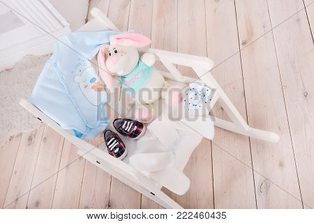 A highchair with toys and clothes for the child. Slips, body, booties