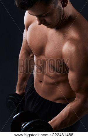 Muscular Bodybuilder Doing Exercises With Dumbbell Over Black Background.strong Athletic Man Shows B