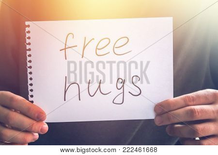 A Man Holds A Note With The Inscription - Free Hugs. Holiday Concept To The International Day Of Hug