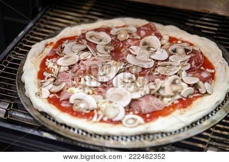 Stages of pizza preparation placing the pizza in the oven