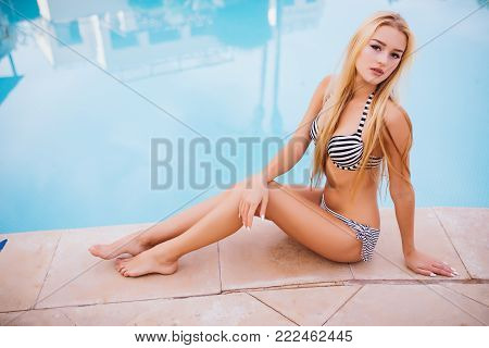 Sexy Young Woman Sitting On The Edge Of A Swimming Pool, Wearing A Bikini While On Vacations In A Su