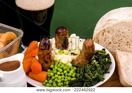 Bangers and Mash A plate of Bangers and Mash, sausage and mashed potato (known as Colcannon) with Irish Stout and Sourdough bread with Stout batter onion rings and a jug of gravy.