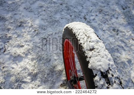 Fat tire bike in winter, bike tire covered in snow, shallow focus