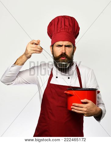 Cook With Strict Face In Uniform Has Casserole With Ladle.