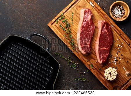Raw fresh meat Picanha steak, traditional Brazilian cut with thyme, garlic, and black pepper on wooden board. Sliced meat steaks with grill iron pan. Top view.