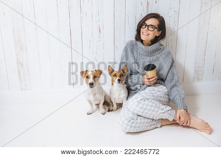 Smiling cheerful young female wears warm woolen sweater, square eyewear, drinks hot beverage, relaxes on floor and her two favourite pets, look directly into camera. People and animals conecpt