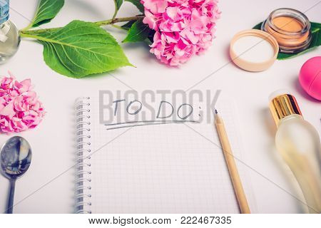 Female working place with To do list, cosmetic accessories, parfumes and wisteria flowers on the white background. Day planning. Fashion, Beauty blog concept