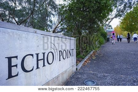 Sydney, Australia - Apr 18, 2017: Stone sign marking Echo Point, Katoomba. The region is part of the Blue Mountains National Park - A UNESCO World Heritage Site. Visitors walking along the footpath.