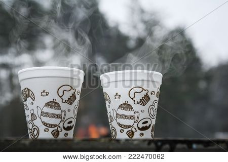 Two cups of hot tea in winter outdoors. Steam rises from the hot beverage. Warmth in the cold