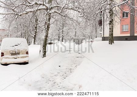 Winter, covered in snow after a Blizzard. A small piece of snow-covered streets. Car, trees covered in snow. In the yard in the snow. The concept of a snowy winter.