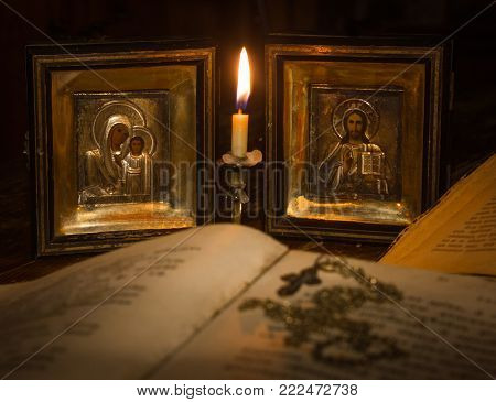Icons of the Mother of God and Jesus Christ with a hymnal and a cross on a bonnet under the light of a candle
