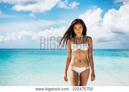Sexy bikini body Asian woman with fit stomach abs and slim waist. Weight loss treatment concept. Beauty swimsuit model lifestyle on beach vacation travel.