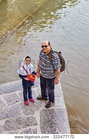 Isfahan, Iran - April 24, 2017: Two-person family, mature adult man and small school-age girl dressed in Islamic school uniform with hijab, poses for photographer against background of  Zayandeh river