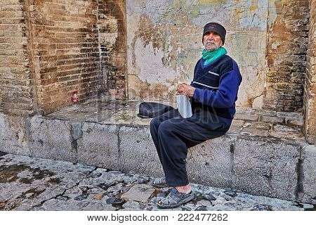 Isfahan, Iran - April 24, 2017: One unknown old man is sitting on the stone seat of the central pavilion of the Khaju bridge.