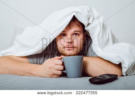 bored man watching TV under the blanket with cup of coffe