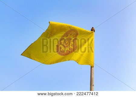 Close up yellow flag of Chakri dynasty against blue sky. The Chakri dynasty is the current ruling royal house of the Kingdom of Thailand.