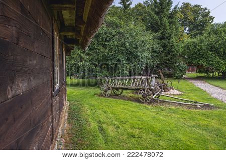 Hay wagon in front of traditional wooden cottage in Masuria region of Poland