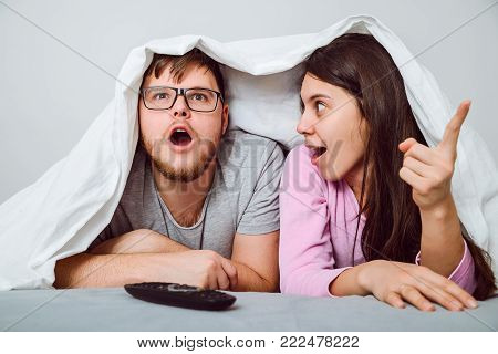 man with woman watchin some interesting movie under the blanket