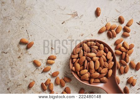 Whole Almonds in a Brown Spoon. Almonds on a table with a brown spoon.