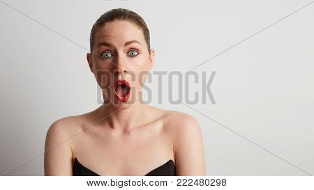 Portrait of shocked young woman with red lips looking to her side