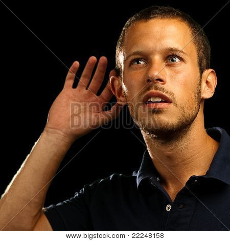 young man hearing sounds on white background