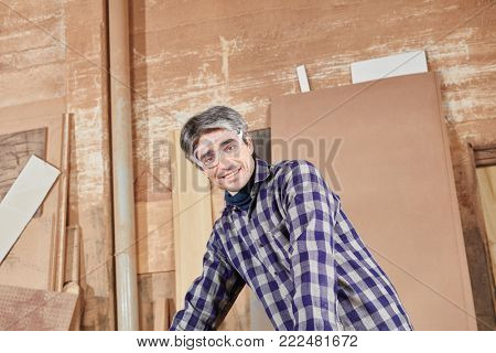 Blue collar worker at workshop working with wood