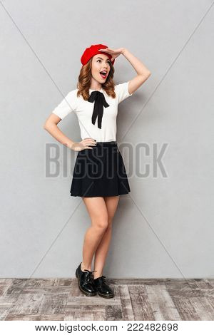 Full length portrait of a pretty schoolgirl dressed in uniform standing and looking far away over gray wall background